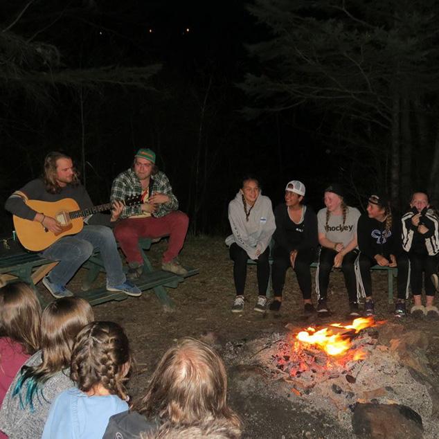 Chansonnier jouant de la guitare avec des enfants qui écoutent autour d'un feu